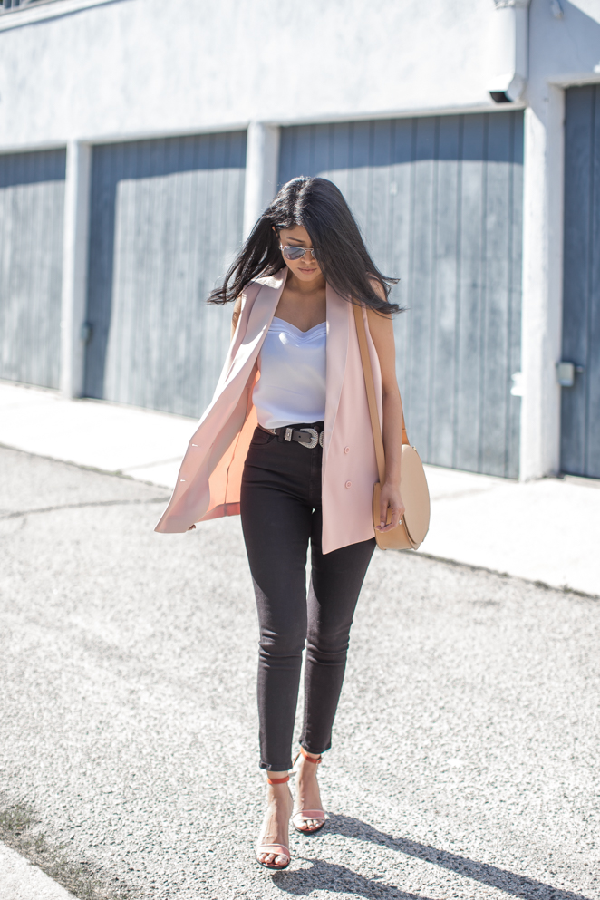 Looking for a hot new spring trend? Try the sleeveless jacket look - a killer style when paired with a simple vest and high waisted jeans! Sheryl Luke is wearing the look in a stylish shade of blush pink for a feminine twist. Jacket/Jeans: Topshop, Cami: French Connection, Bag: Cuyana, Shoes: Dear Frances, Belt: Linea Pelle.
