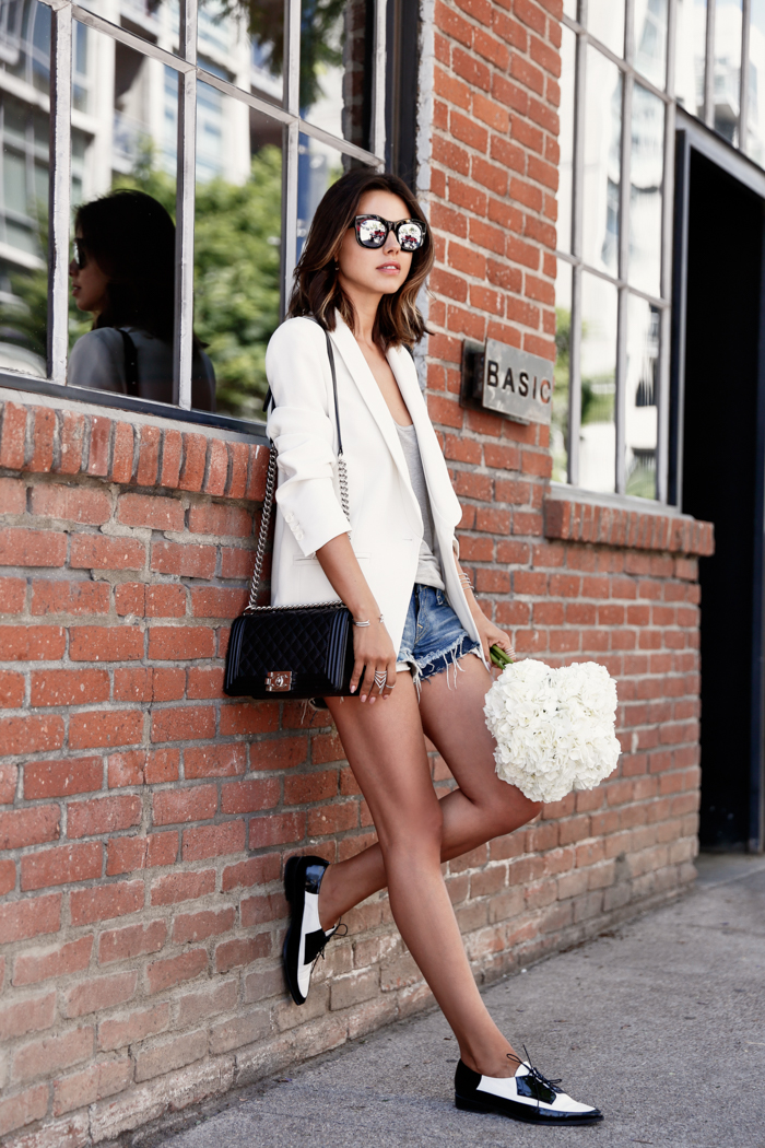 Loafers are back this season, and they're taking the fashion world by storm! Annabelle Fleur wears a pair of classic black and white patent loafers here, which act as a statement piece worn with simple denim shorts and a pastel pink blazer. Shoes: Stuart Weitzman, Blazer: IRO, Bag: Chanel.
