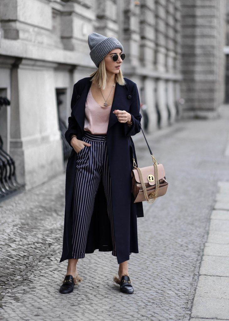 Aylin Koenig has created the ultimate everyday style here, pairing authentic leather loafers with striped cropped trousers and a plunge neck tee for a cool street style! Wear this look with an oversized or trench coat to give the look that winter edge! Coat/Trousers: MAX&Co, Top: Alix via Net-A-Porter, Shoes: Gucci, Bag: Chloé via Net-A-Porter, Beanie: ACNE Studios, Sunnies: Ray-Ban, Necklace: Chanel.