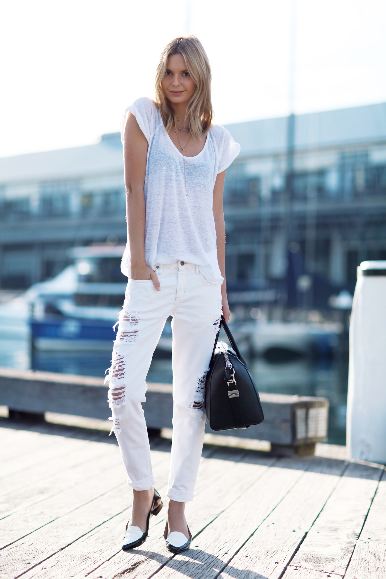 All white looks are a must-have for your summer wardrobe. Jessica Stein is a vision in white, wearing a pair of distressed jeans with a plain tee and a pair of gorgeous monochrome loafers. T-Shirt: Zara, Jeans: Nobody, Loafers: Fabio Rusconi, Bag: Givenchy.