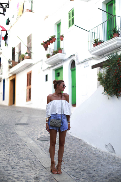 Silvia Garcia is looking effortlessly chic in this gorgeous off-the-shoulder white top, and cute striped skorts. Styled with heeled sandals, and some bold bangles creates a fab summer outfit. We love this! Top-Zara Skorts- Storet Shoes- Senso Bag- Gucci