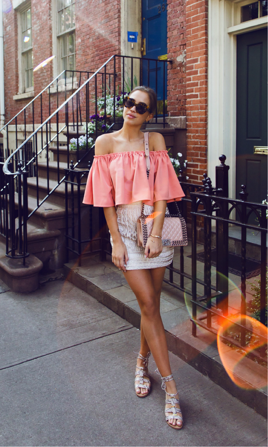 This is the ultimate summer outfit! Kenza Zouiten looks pretty-in-pink in this off-the-shoulder tee and mini skirt combo. We love the pairing of the different shades of pink, which make for an adorable feminine look. Top: Revolve, Skirt: Ginatricot, Sandals: Steve Madden