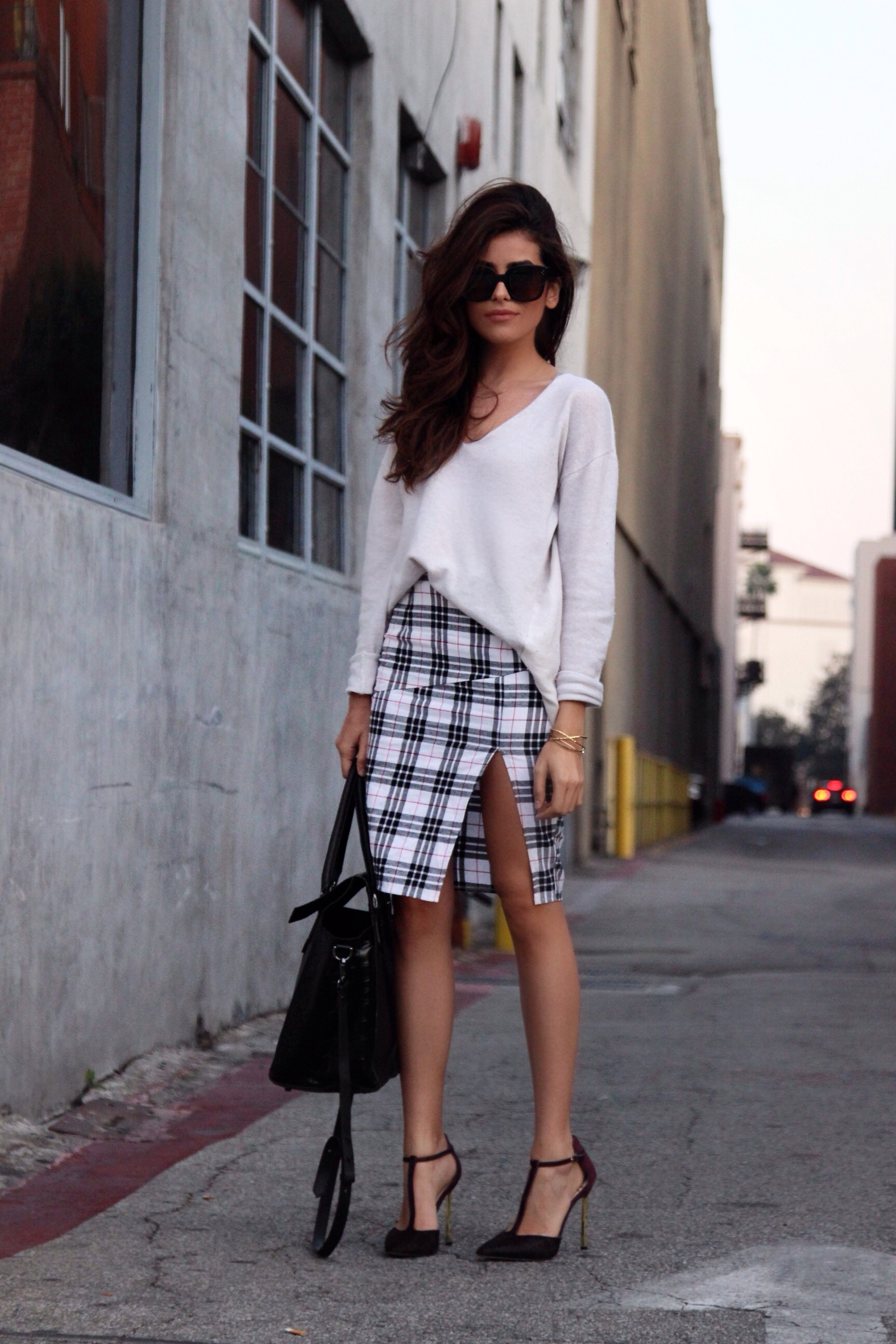 Sazan Barzani is taking sexy to new heights with this tartan pencil skirt and high thigh slit! With a t-strap stiletto and an oversided (thin) sweater, you too can turn an otherwise relaxed look into a eyecatching outfit! Skirt: Shop Luna B., Top: Margaret O'Leary, Shoes: Sam Edelman, Purse: Treesje, Sunglasses: Celine, Bracelet: Gorjana