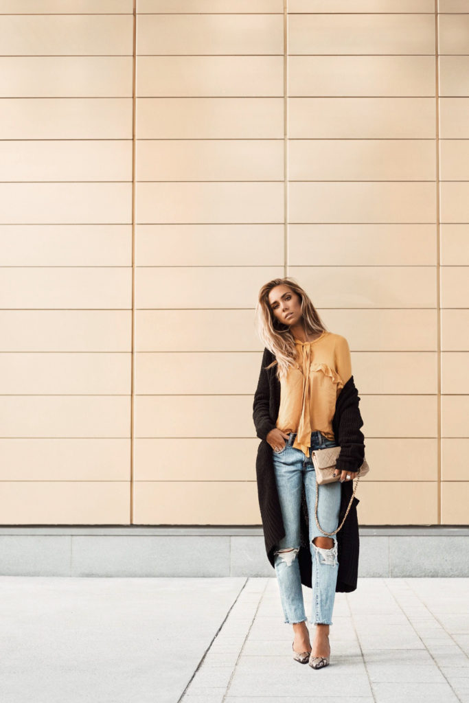 Lisa Olsson layers a cozy long line cardigan over her neutral blouse and distressed jeans. The tones are neutral and this look can be worn in the day with flats or in the evening with heels. Shoes: Ecco