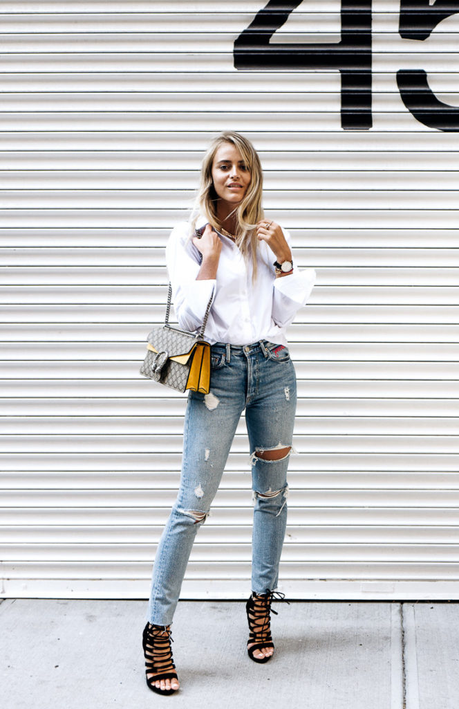 This look is classic yet fun. Jannie Deler adds a pop of color with her Gucci bag; her statement strappy sandals also add some interest to her outfit. This look can also be worn with grey or black skinnies as an alternative.