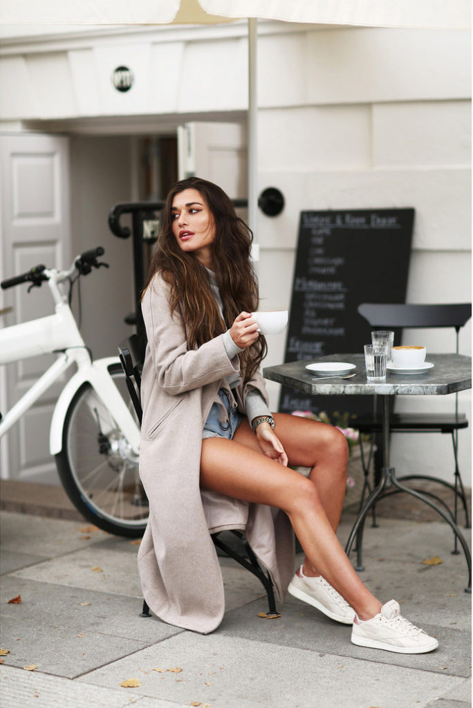 Ilirida wears classic Levi shorts paired with cream sneakers for a casual daytime look; she takes this summer look into fall by adding a long beige coat. Jacket: ASOS, Shorts: Levi, Sweater: Pieces, Sneakers: Reebok