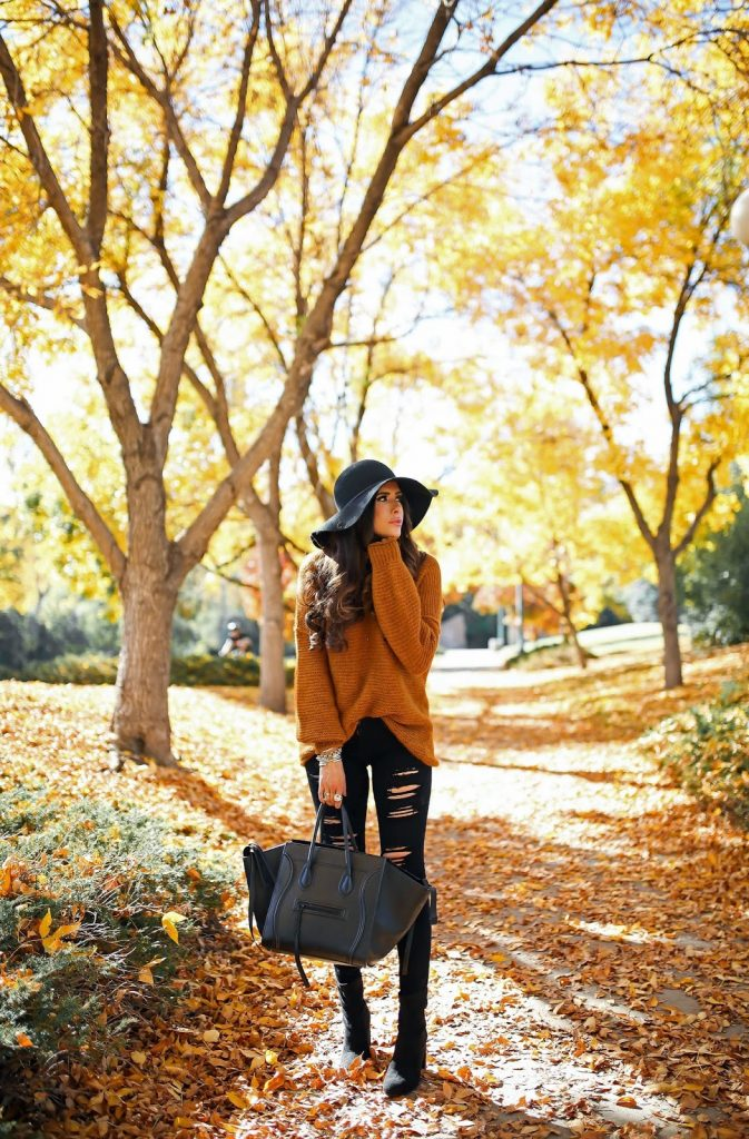 Emily Ann Gemma couldn't look more cosy in this autumnal knitted sweater, worn with distressed black jeans and a wide brimmed black hat for an elegant style with an individual edge. Sweater: Free People, Jeans: AG, Boots: BCBG.