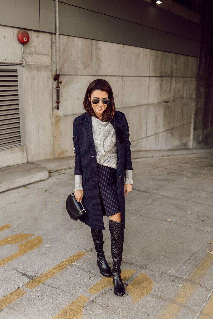 Rocking a boyish chic style, Christine Andrew is wearing a pinstripe two piece consisting of a skirt and coat, paired with a knit sweater and thigh high boots, creating this striking fall outfit. Coat/Skirt: Marissa Webb, Sweater: ILY Couture.