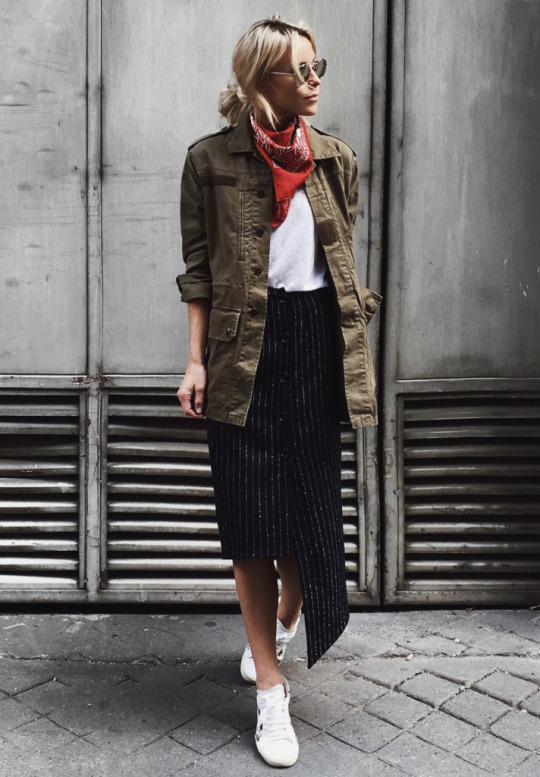 Mary Seng looks effortlessly edgy in this oversized military style jacket, worn with a red neckerchief and an asymmetrical midi skirt. This look is perfect for everyday wear, and will absolutely create an impression! Blouse: Isabel Marant, Trousers: Burberry.