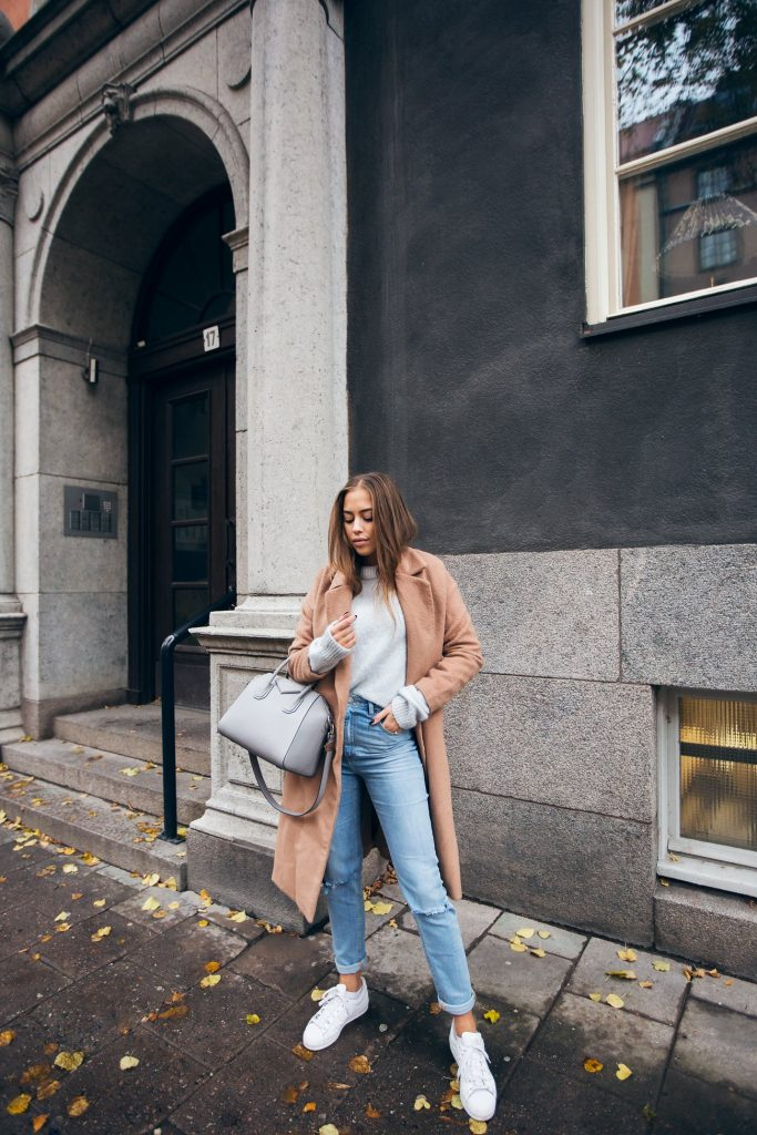 Kenza Zouiten is killing this casual fall style, consisting of a gorgeous camel overcoat, jeans, and a pair of white sneakers. An outfit such as this just screams laid back chic! Jeans: Asos, Coat: Make Way, Sweater: Ivy Revel, Coat: Make Way, Shoes: Adidas.