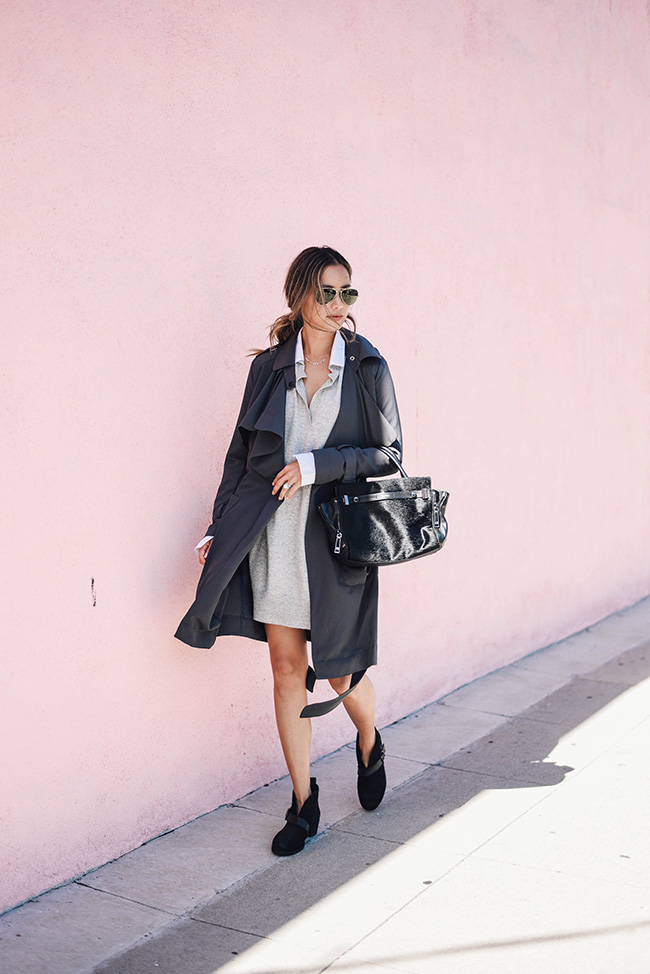 Jamie J Chung looks casually sophisticated in a collared shirt dress, a grey trench coat, and a patent leather bag. Wear this style with ankle boots to achieve these elegant vibes! Boots: Ugg.