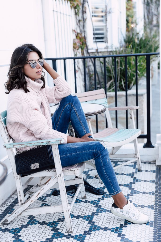 Annabelle Fleur keeps it casual in a chunky knitted sweater, distressed jeans, and a pair of star-studded sneakers. We recommend this kind of style for a chilled day in the city, or a fresh faced country walk! Brands not specified.