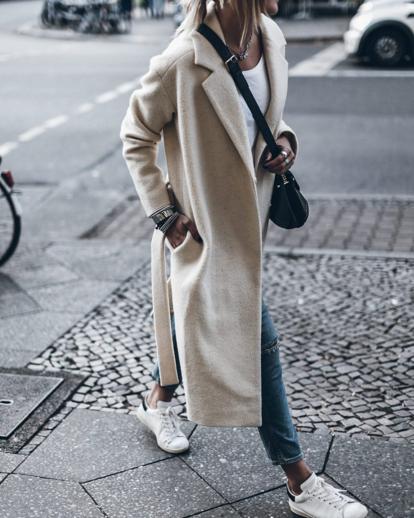 Jacqueline Mikuta wears a super stylish cream maxi coat with distressed denim jeans and sneakers to create this cute fall look. Give this style a try with a plain tee to capture these casual vibes! Coat: Designers Remix, Jeans: GRLFRND, Shoes: Isabel Marant, Tee: The Kooples.