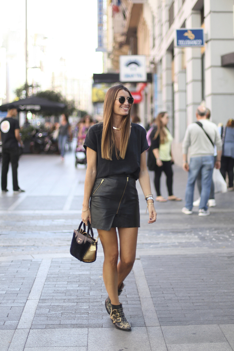 Silvia Garcia looks absolutely stunning in her diagonal zip leather mini skirt paired with buckled booties and simple black top. This contemporary mini and all that goes with makes a style as chic as it is rebellious. Mini skirt: Asos, Top: Anine Bing, Shoes: Chloe, Purse: Longchamp