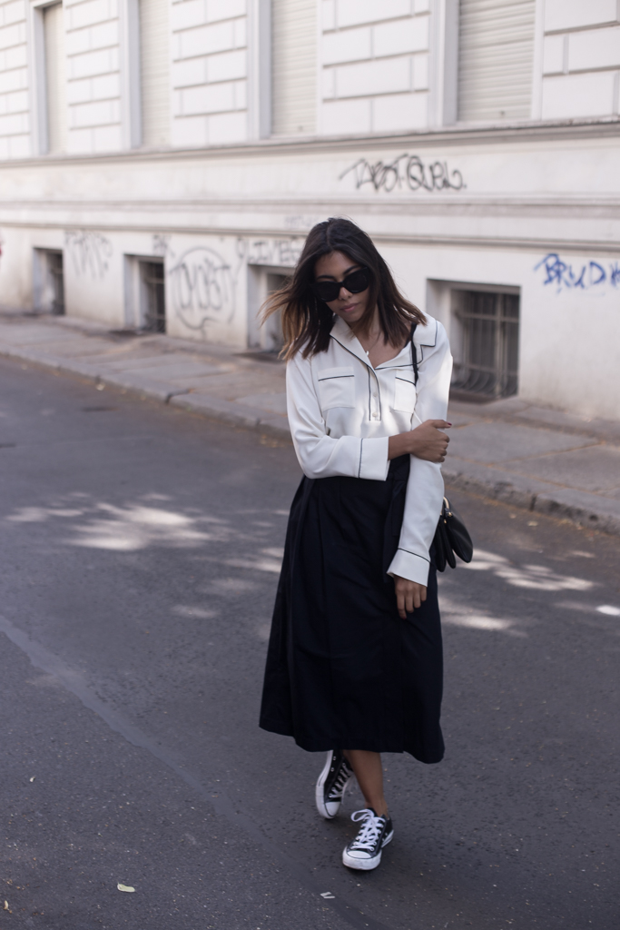 Storm styles her pyjama shirt with a midi skirt and sneakers. By adding a pair of sunglasses, a designer bag and dainty jewelry, she channels effortless cool. Blouse: & Other Stories X Rodarte, Skirt: 3.1 Phillip Lim, Sneakers: Converse, Bag: Céline