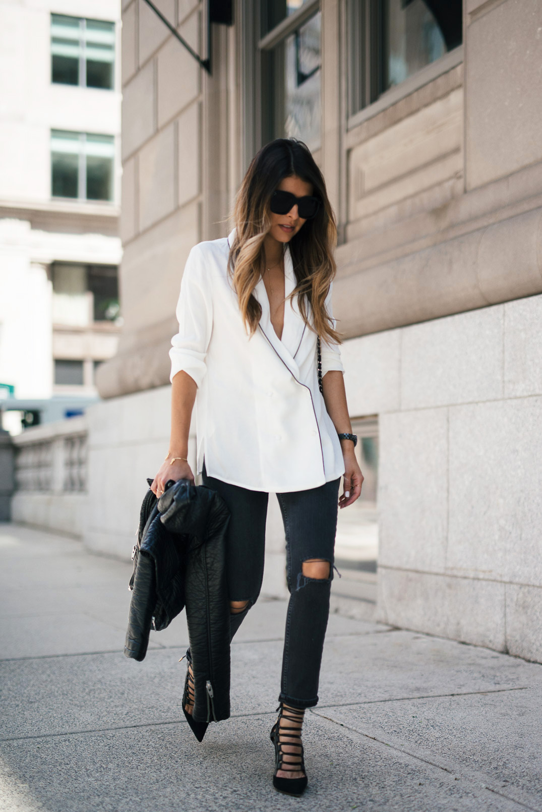 Pam Hetlinger plays with proportions by teaming up her silk oversized pyjama inspired shirt with ripped skinny jeans. She adds some height with lace up heels and a trusty leather biker jacket for that flawless city style. Top: Mango, Jeans: Asos, Watch: Chanel, Necklace: The Girl From Panama x Mejuri, Heels: Aquazzura