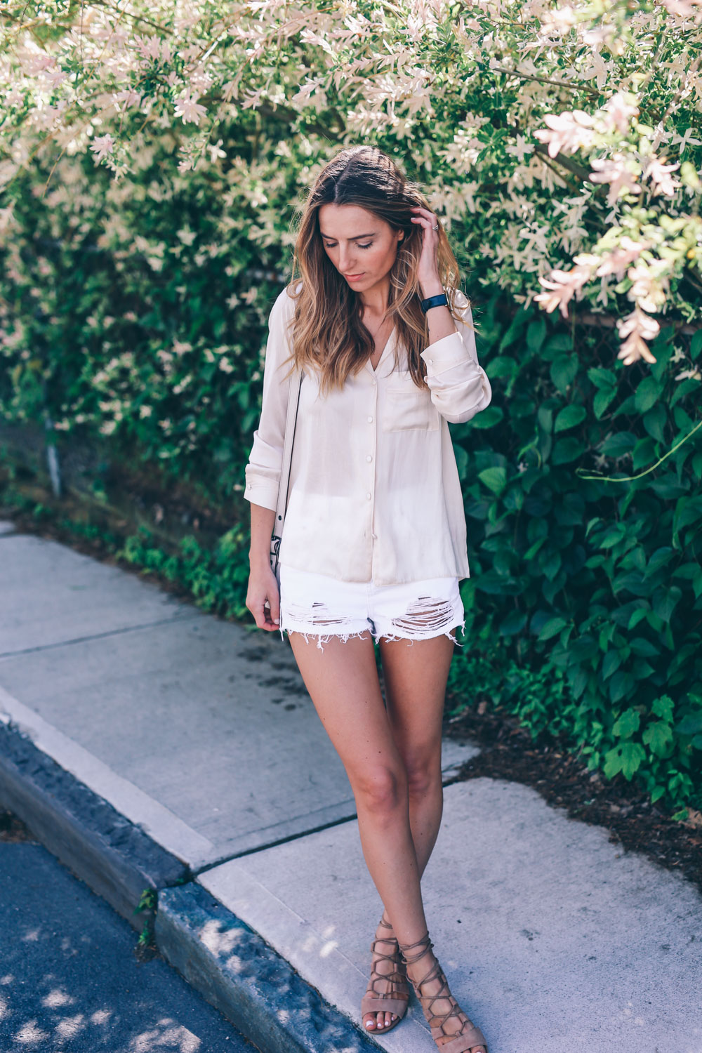 Jess Ann Kirby wears her blush nude pyjama shirt with distressed shorts, finishing off the perfect feminine summer look with beachy waves and gladiator sandals. Shirt: Topshop, Short: Topshop, Shoes: Steve Madden, Watch: Larsson & Jennings, Bag: Coach (All items from Nordstrom)