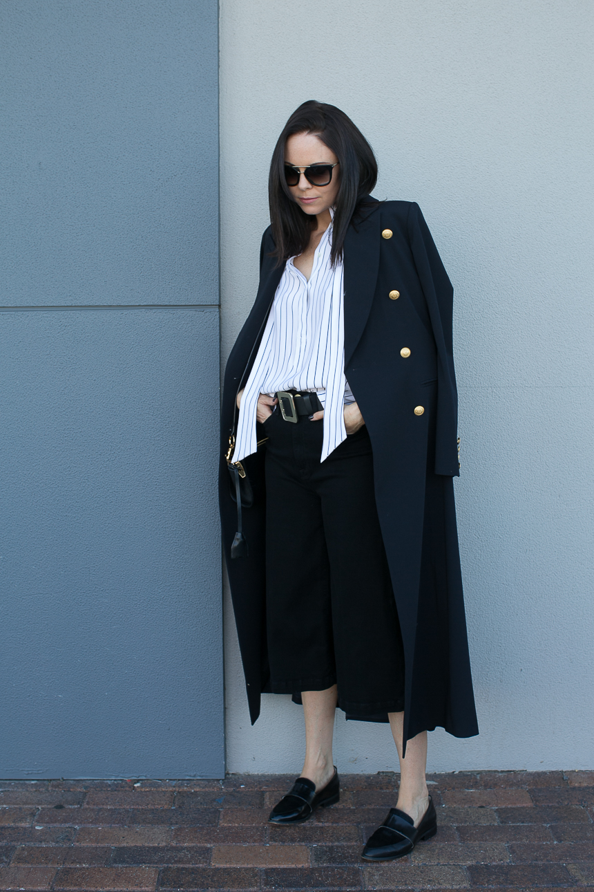 Fiona Bassingthwaighte's masculine silhouette combines wide legged pants over this awesome military coat. Softened by the striped shirt and refined loafer, the trench coat shows this lady means business. Coat: Hunky Dory, Shirt, Pants and Belt: FRAME, Tank: Enza Costa, Bag: Alexander Wang, Shoes: Witchery, Sunglasses: Prada.