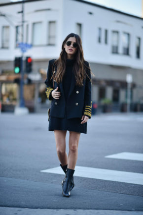 Paola Alberdi has created a monochromatic look, with accents of gold in both the buttons and braiding of this military jacket. She places the jacket over a ribbed knit dress and finishes the look with patent heeled ankle boots and Ray Ban aviators. Jacket: Storets, Dress: UK Glamorous, Sunglasses: Raybans, Chloe: Handbag, Shoes: Max Mara