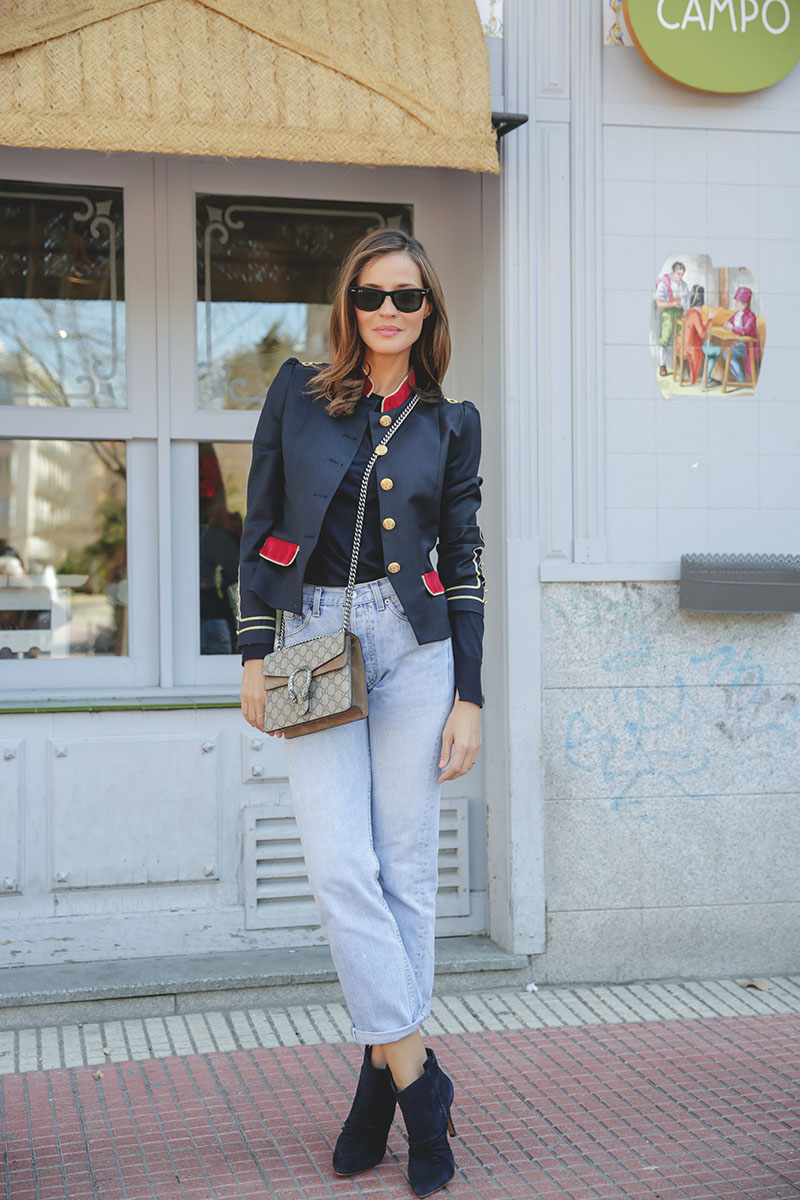 Silvia Zamora's look is both chic yet causal. Her military jacket is paired with high-waisted distressed jeans, a dark sweater and to die-for blue suede ankle boots. The gold piping and buttons are major players this season. Military jacket: La Condesa, Sweater: Zara, Jeans: Levi's, Vintage bag: Gucci Dionysus boots: IKKS