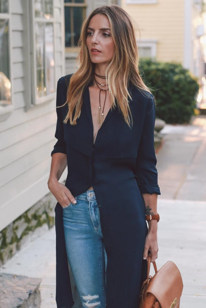 At the height of casual luxury, Jess Ann Kirby pairs a multi-layered choker with gold tassels with a deep v-neck trench dress. We want to join her for brunch by the seaside! Trench dress: AYR, Choker: Capwell, Jeans: Paige Denim, Bag: Brahmin