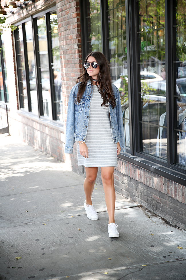 Ready for a Sunday morning stroll downtown, Lizzy van der Ligt sports white sneakers, a denim jacket, and subdued horizontal stripes in heather grey. This versatile Fallon choker is an excellent touch, combining diamond vines and leather strips. Dress: Lou & Grey Vintage, Sneakers: Kenneth Cole, Choker: Fallon, Sunglasses: Quay