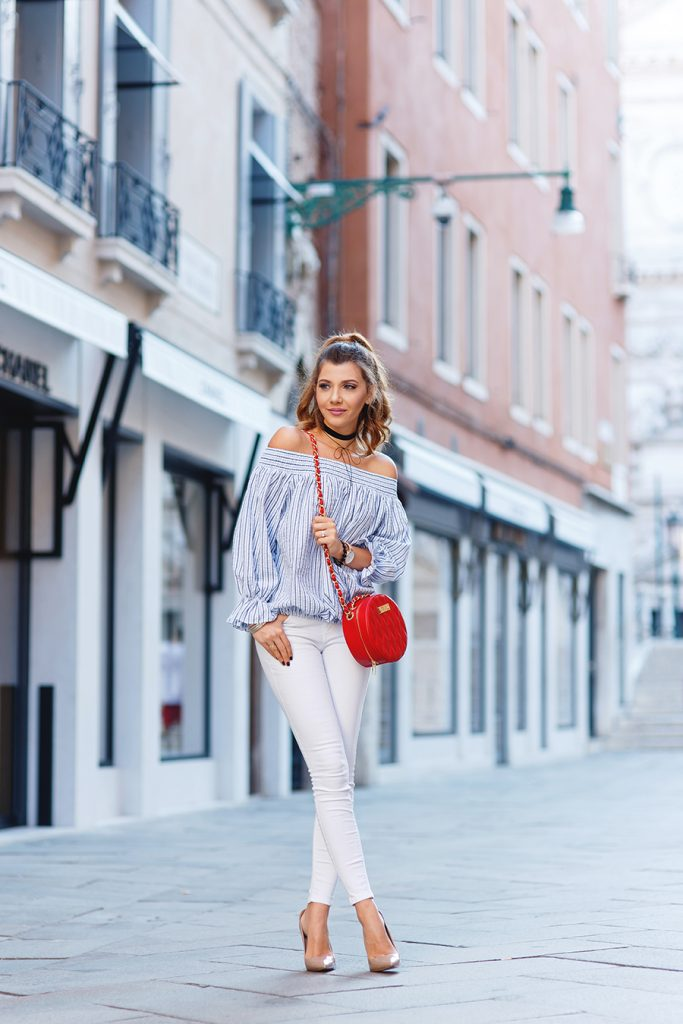 Showing off playful streetwear, Larisa Costea accessorizes slim white jeans with a quilted red cross-body, nude pumps and plenty of jewellery. Her adorable off-the-shoulder peasant top is balanced by two slim black chokers. Shirt: Chicwish, Jeans: Zara, Shoes: Kurt Geiger, Bag: Concept 15, Watch: MVMT, Chokers: Shein and Miss Mary a Little