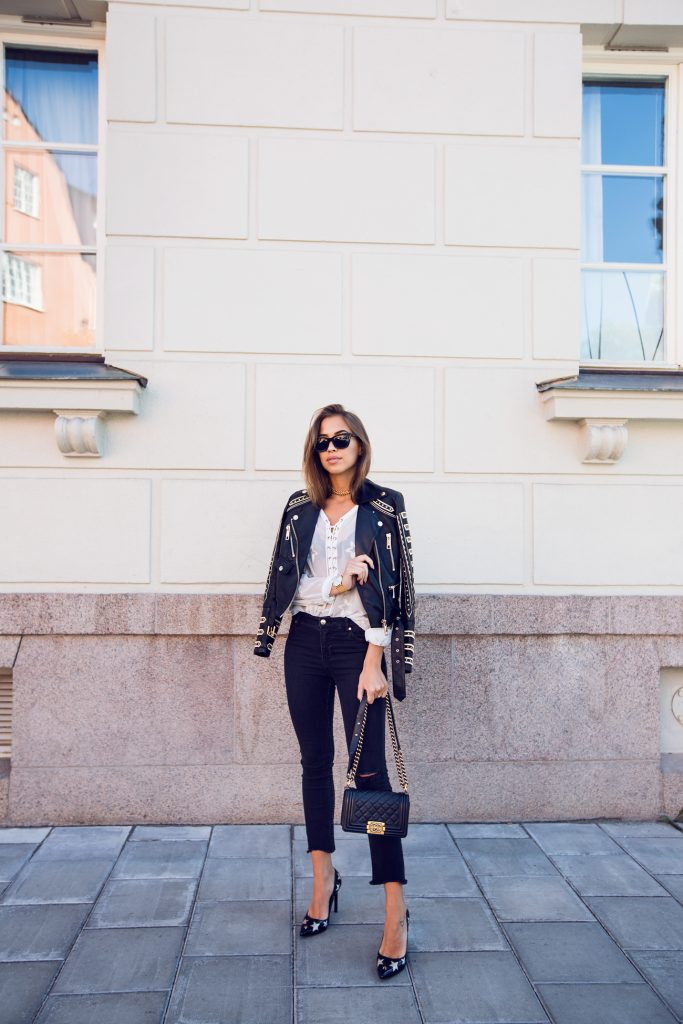 Gold is everything for Kenza Zouiten in this rockstar-worthy wardrobe, featuring an ultra embellished leather jacket, lace-up blouse and chainlink choker. Can you believe these amazing heels? Pants, Jacket, Choker and Shoes: Ivyrevel, Blouse: Ginatricot, Bag: Chanel, Sunglasses: Prada, Watch: Larsson & Jennings