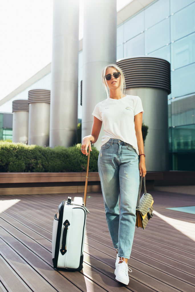 Janni Deler's classic white tee and denim jean is as a street style staple as well as a great choice for travel. This chilled out vibe is dressed up with a pair of cool shades and stylish designer handbag. Top: Bik Bok, Jeans: Chiquelle, Bag: Gucci, Shoes: Senso, Travel bag: River Island