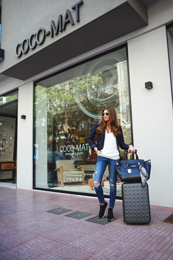 Larisa Costea instantly smartens up her travel outfit with a cropped blue blazer and designer handbag. Blazer: Reserved, Top: Shein, Jeans: Zara, Sneakers: Axel Arigato, Bag: Concept 15 Harper, Watch: Kapten and Son
