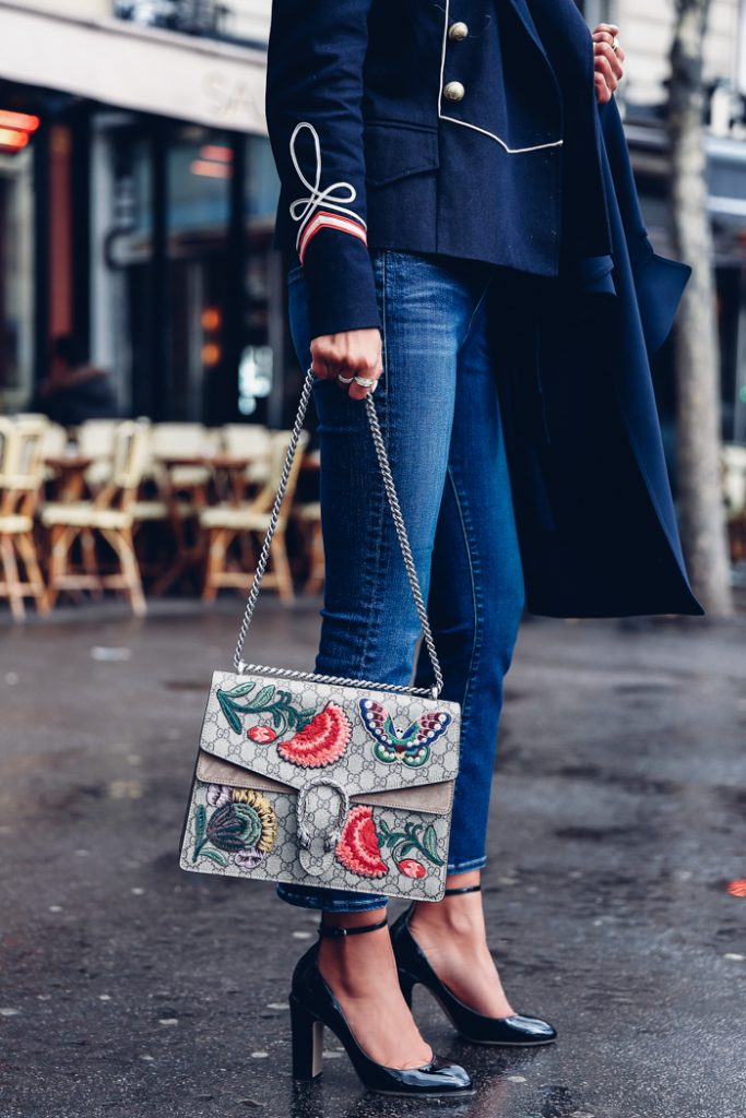 Annabelle Fleur makes the most of the embroidered trend with the richly coloured flowers and butterflies across her Gucci Dionysus bag. Extra embroidered details are also found on the cuffs of her military-style jacket. The slim line jeans, scarlet shirt, trench coat and strappy heels all help to add a classy edge to the overall look. Milford Navy Suits Jacket: Etoile Isabel Marant, Cropped Slim-Leg Jeans and Blouse: Frame, Tango Pump: Valentino, Oakland B Trench Coat: Theory, Dionysus Embroidered GG Canvas Shoulder Bag: Gucci, Set of 5 Rings: Rachel Zoe.