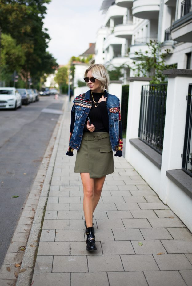 Lisa RVD wears a BoHo chic jacket with embroidered flowers on the sleeves and gold coin and flower motifs on the front. She keeps the rest of this look simple with a black knit and olive asymmetric mini, helping to emphasise the jacket. A great pair of Balenciaga boots give the outfit an overall girly grunge flavour. Jacket: Desigual, Knit: Reserved, Skirt: Storets, Boots: Balenciaga, Sun Glasses: Céline, Jewellery: Ariane Ernst.
