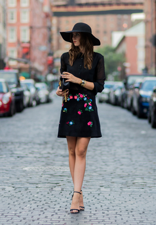 This is a twist on this season's monochrome look but with the addition of embroidered motifs on the mini skirt. The look is finished with a simple black button through shirt, black handbag with contrasting gold chain, and a large brimmed hat to create a chic and feminine style.