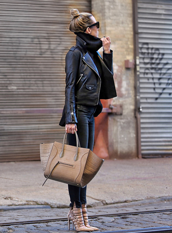 A black outfit of leather and denim is complemented by nude accessories. The volume of the turtleneck is balanced by her topknot bun hairstyle. Via Helena Glazer Jacket: Mackage, Sweater: Banana Republic, Pants: Rag & Bone, Shoes: Aquazzura, Bag and Sunglasses: Céline