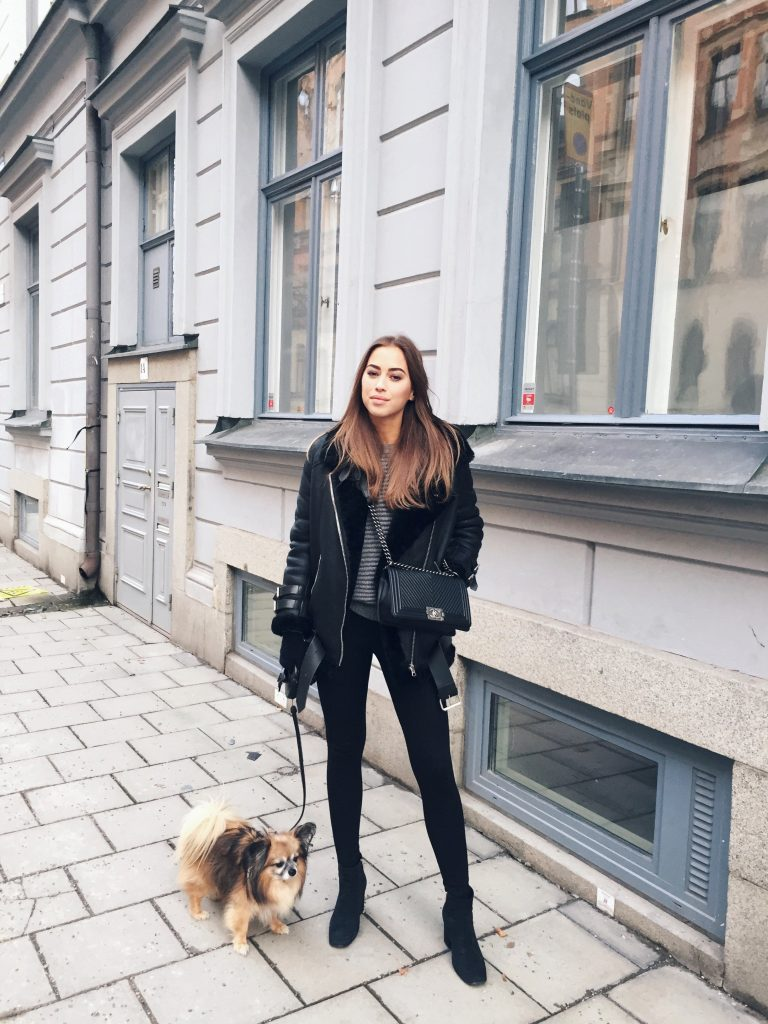 Kenza Zouiten keeps it smart casual in this gorgeous monochrome style, consisting of a striped tee, shearling suede jacket, and a pair of simple leggings. Wear this look with a cross body bag to steal Kenza's style. Jacket: Acne Studios, Tights: Ginatricot, Sweater: Make Way, Bag: Chanel, Boots: Anine Bing.