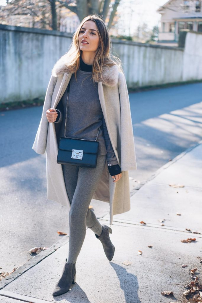 Jess Ann Kirby is the ultimate image of winter glamour in this outfit, consisting of grey marl leggings and a matching top, a leather cross body bag, and a gorgeous coat with a faux fur collar for that warmth you crave. Brands not specified.