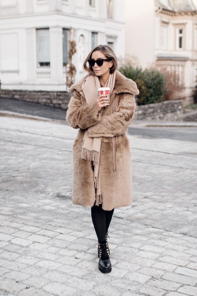 Nothing screams winter chic more than a faux fur coat! Emilie Tømmerberg looks a dream in this gorgeous camel piece, worn with chunky black laced boots and tights for an edgy take on a classic look! Brands not specified.
