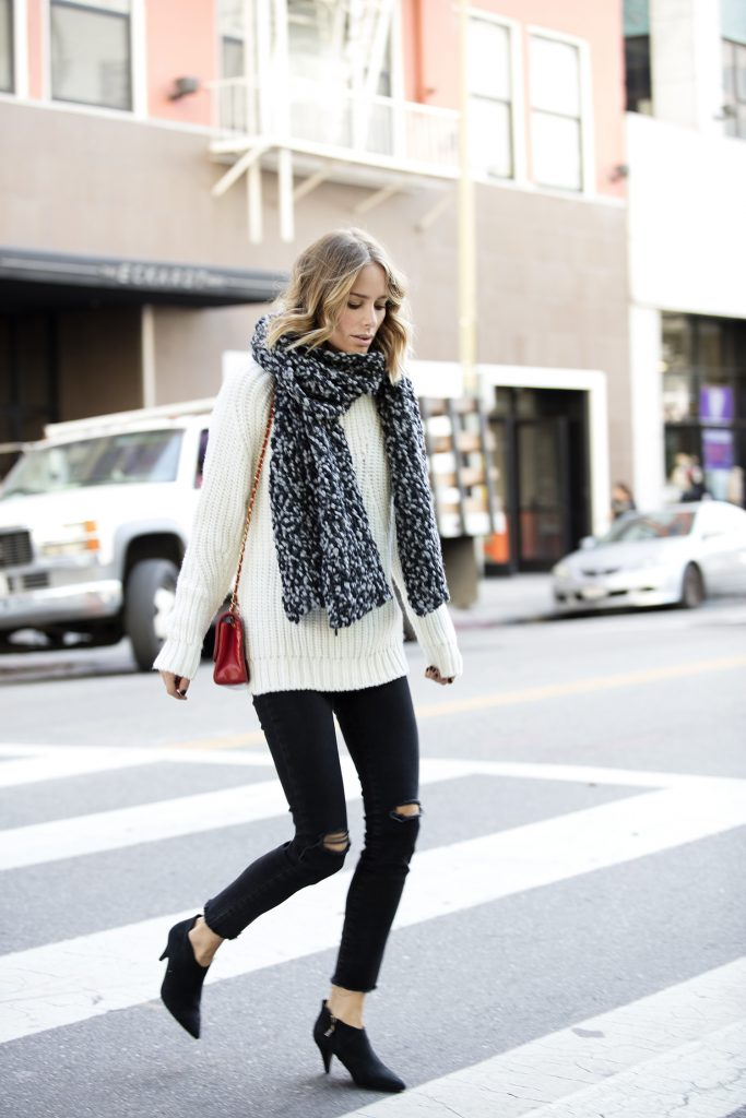 Anine Bing opts for a chunky salt-and-pepper speckled knit scarf and a little red bag for a pop of colour. Black skinny jeans with worn-through knees are the go-to streetwear pants of the moment. Scarf, Jeans, Boots: Anine Bing, Bag: Chanel
