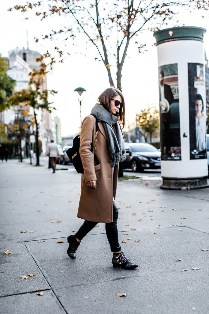 Gold details add interest to this lux street style. Nina looks iconic in an exquisite camel coat and leather leggings. Coat: Marc'o Polo, Scarf: Acne, Shirt: Asos, Pants: BCBGMAXAZRIA, Boots: Bronx, Bag: Saint Laurent, Sunglasses: Le Specs