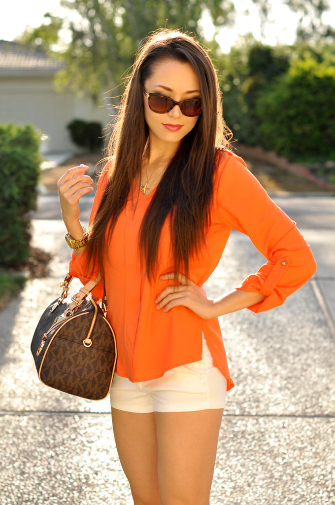 Jessica Norcal Is Wearing An Orange Blouse From Sheinside, Shorts From Pacsun, Sunglasses From Versace, And The Bag Is From Michael Kors