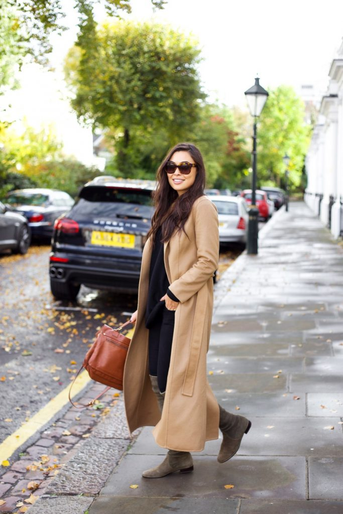 Kat Tanita is sleek and sophisticated in this gorgeous classic camel coat, worn with black jeans and over the knee suede boots for a chic everyday style. Wear this look with a leather bag and shades to complete the outfit! Coat: Tempo, Sweater: Vince, Jeans: Paige, Boots: Stuart Weitzman, Bag: Proenza Schouler.