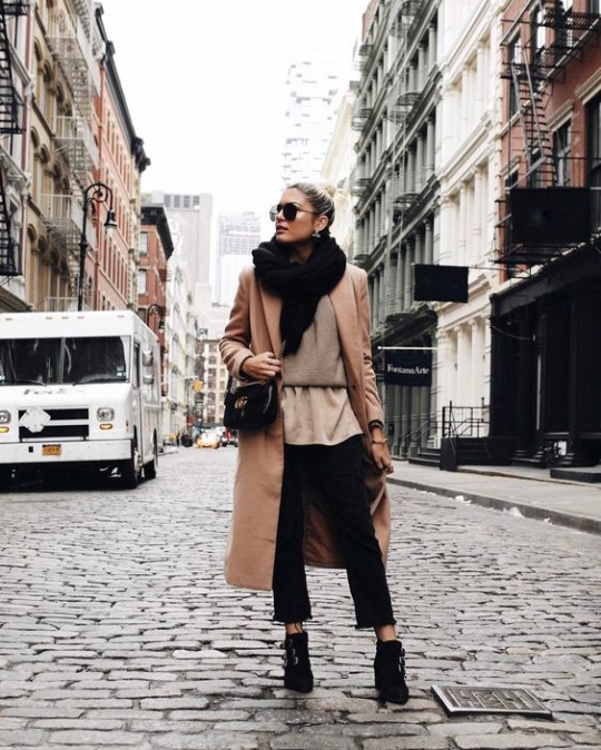 Emily Luciano wears a camel coat with layered tops of beige tones, and cropped black cigarette trousers. She finishes the look with a chunky oversized scarf and punk-esque black heeled boots.   Coat: Forever 21, Top: Vince, Trousers: Zara.