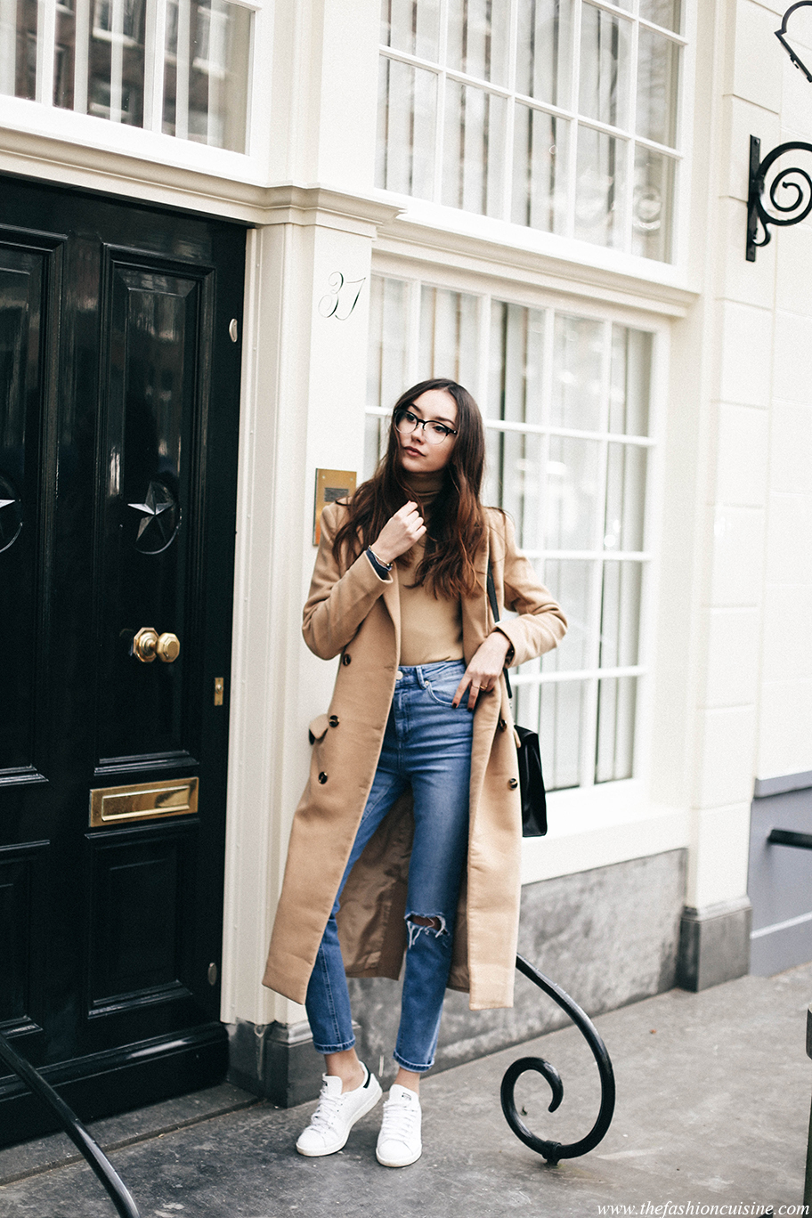 Beatrice Gutu looks ultra chic in this retro outfit consisting of a maxi camel coat, distressed high waisted jeans, and a pair of classic Adidas Stan Smith sneakers. Coat: Missguided, Turtleneck: Zara, Jeans: Asos, Sneakers: Adidas.