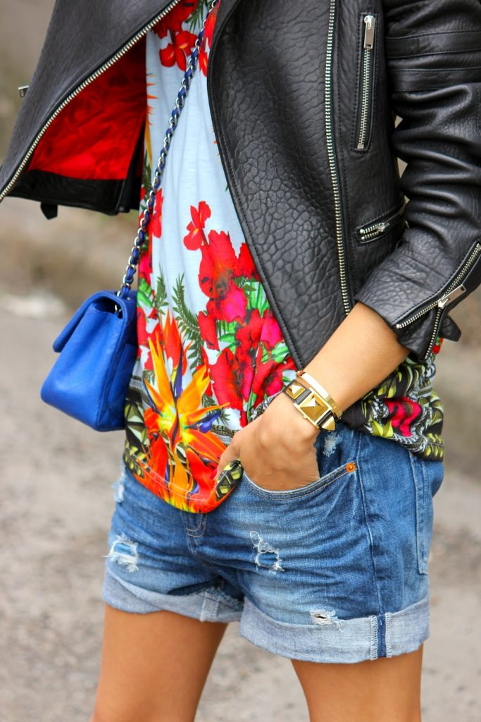 Givenchy Floral Top With Cutoff Denim Shorts, With A Leather Jacket And A Blue Chanel bag Via They All Hate Us