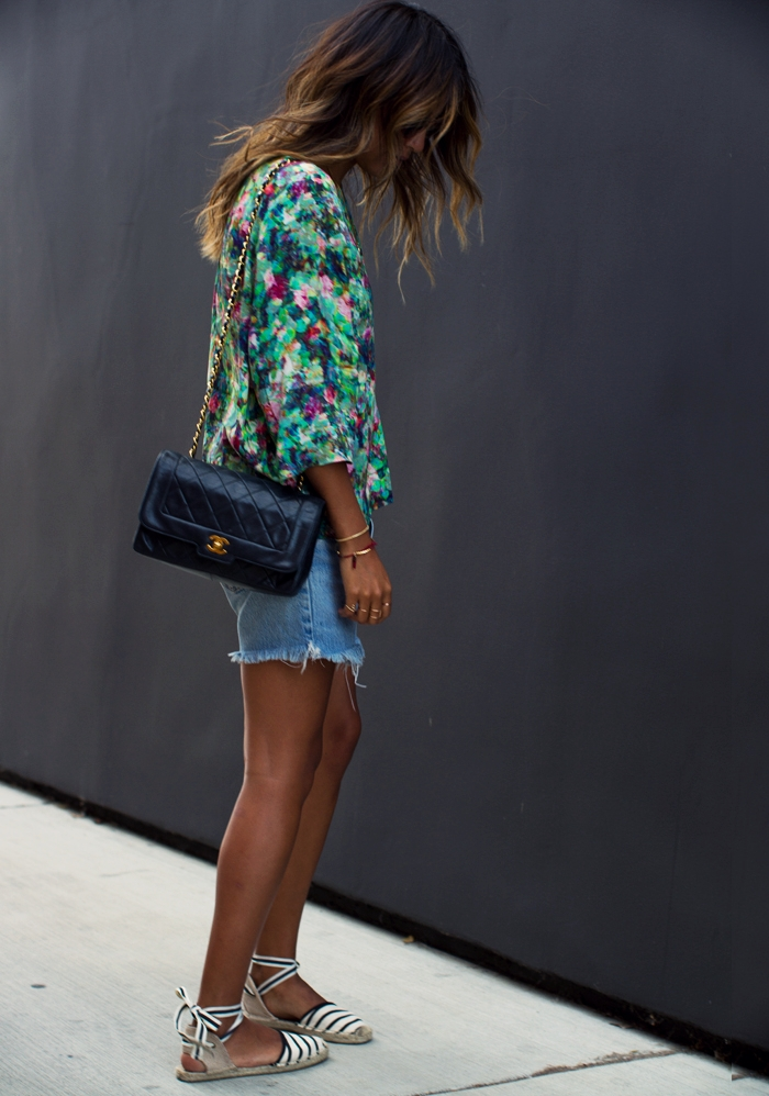 Julie Sarinana is wearing a floral blouse from Sam & Lavi, distressed denim short from Levi's, espadrilles from Soludos, vintage bag from Chanel and sunglasses from Raen