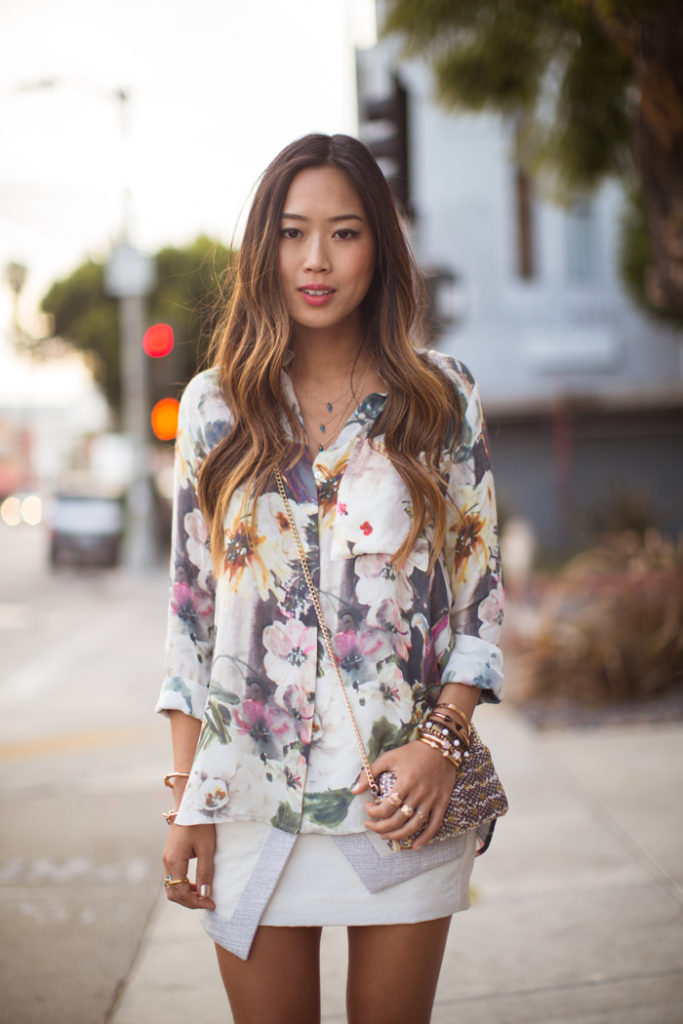 Aimee Song is wearing a white asymmetrical skirt and floral shirt from Finders Keepers