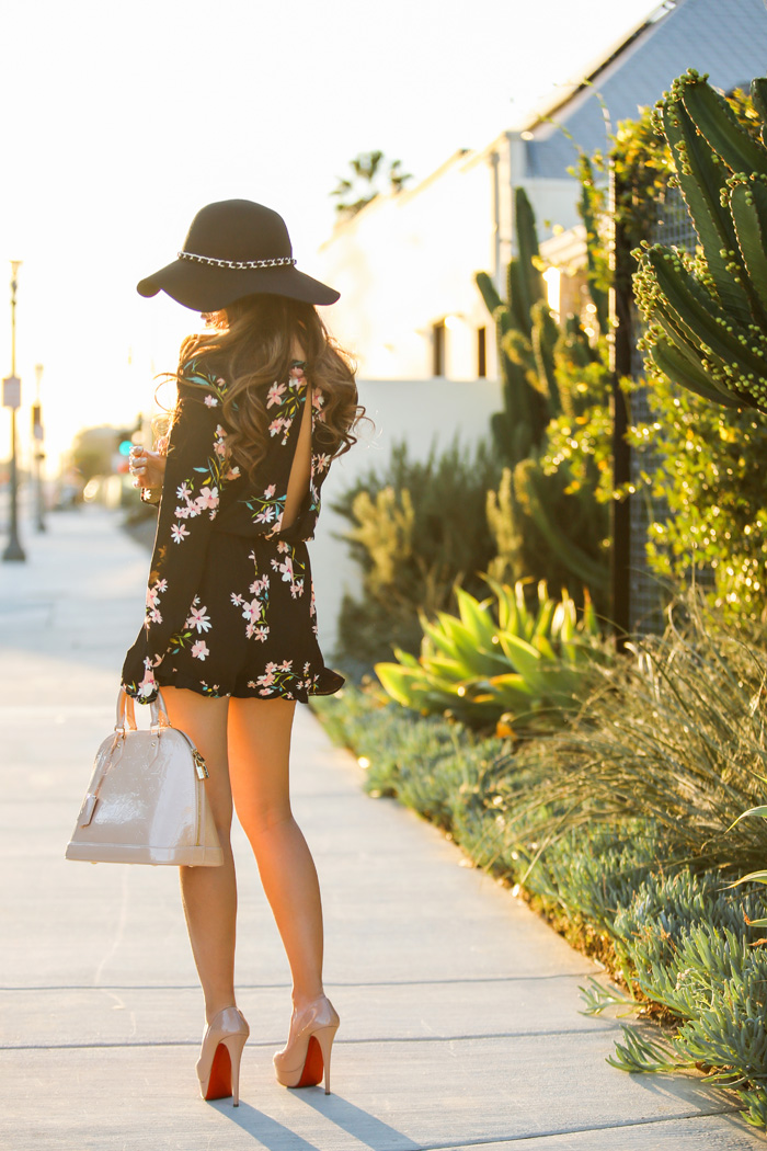 Kim Le is wearing floral romper from Urban Outfitters, bag from Alma PM and shoes from Christian Louboutin