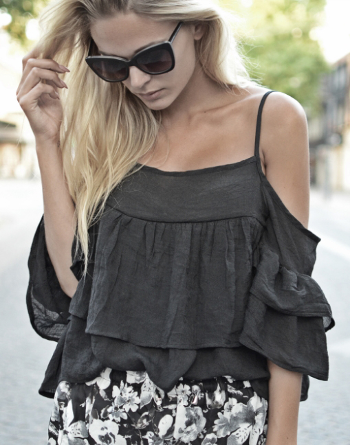 Tina Maria is wearing a black ruffle top and black and white floral chiffon shorts from from Sheinside and sunglasses from & Other Stories
