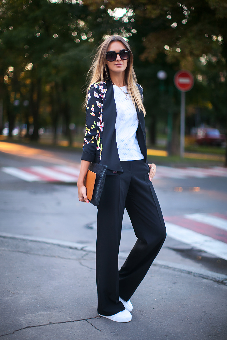 Nika Huk is wearing a floral blazer from Girls on Film, top from Zara, pants and sneakers from Asos, clutch from Clare Vivier, and sunglasses from Zero UV