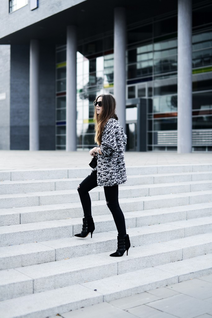 Cindy Van Der Heyden Is Wearing Black And White Knitted Cardigan From H&M, Black Ripped Zara Jeans, Boots By Isabel Marant Proenza Schouler PS11 Tiny Bag And Sunglasses From Saint Laurent